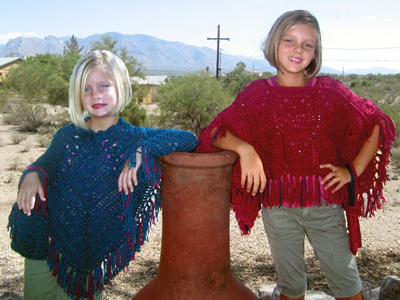Two girls wearing custom-knitted ponchos of indigo blue and cranberry, press space or enter to visit gallery